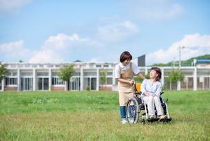 車椅子を押す介護士の女性の写真素材 [FYI03457436]