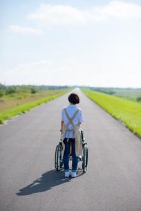 車椅子を押す介護士の女性の後ろ姿の写真素材 [FYI03457442]