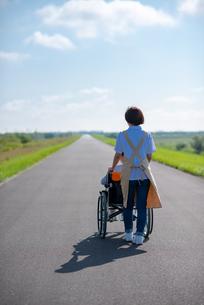 車椅子を押す介護士の女性の後ろ姿の写真素材 [FYI03457443]