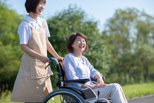 介護士に車椅子を押してもらうシニア女性の写真素材 [FYI03457450]