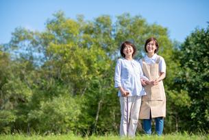 シニア女性の歩行を介助する介護士の写真素材 [FYI03457453]