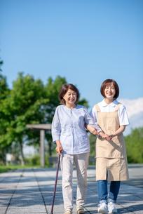 シニア女性の歩行を介助する介護士の写真素材 [FYI03457457]