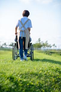 車椅子を押す介護士の女性の後ろ姿の写真素材 [FYI03457459]