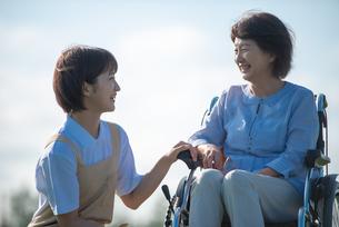 車椅子のシニア女性に寄り添う介護士の写真素材 [FYI03457462]
