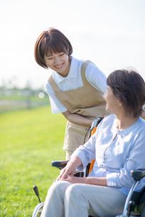 車椅子のシニア女性に寄り添う介護士の写真素材 [FYI03457464]