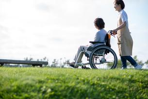 車椅子を押す介護士の女性の写真素材 [FYI03457466]
