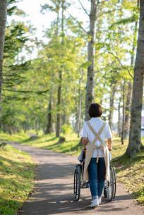 車椅子を押す介護士の女性の後ろ姿の写真素材 [FYI03457467]
