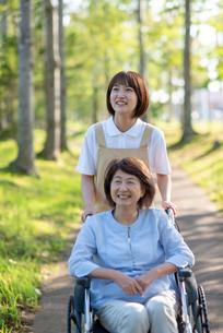 車椅子を押す介護士の女性の写真素材 [FYI03457468]