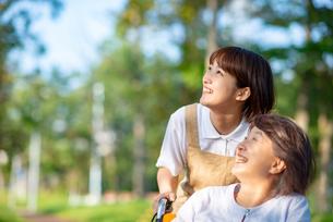 空を見上げるシニア女性と介護士の写真素材 [FYI03457474]