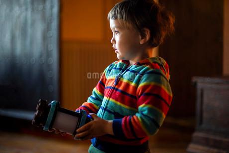 ハーフの幼児が屋内でおもちゃを手に持ち何かを見つめる様子の写真素材 [FYI03457729]