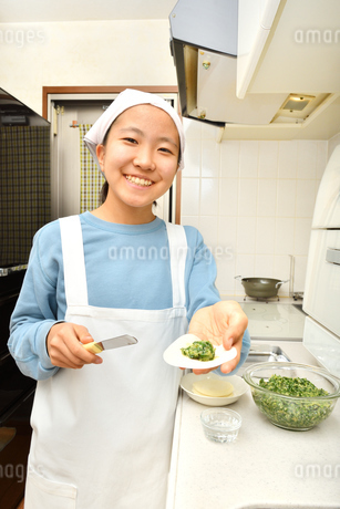 キッチンで料理をする女の子の写真素材 [FYI03457911]