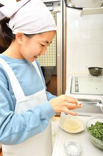キッチンで料理をする女の子の写真素材 [FYI03457912]