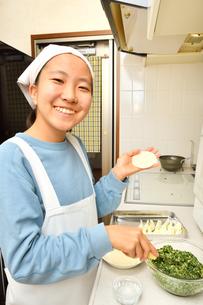 キッチンで料理をする女の子の写真素材 [FYI03457913]