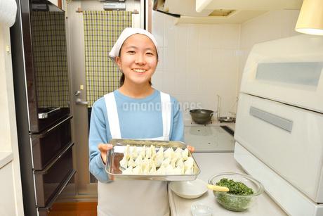 キッチンで料理をする女の子の写真素材 [FYI03457916]