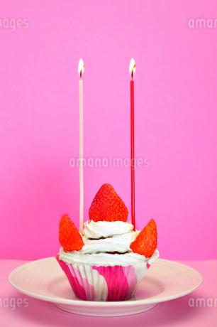 ロウソクの灯ったカップケーキの写真素材 [FYI03458702]