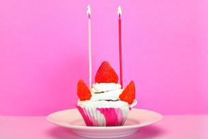 ろうそくの灯ったカップケーキの写真素材 [FYI03458706]