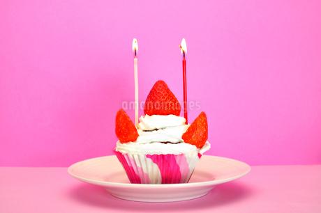 ろうそくの灯ったカップケーキの写真素材 [FYI03458708]