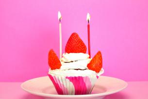 ろうそくの灯ったカップケーキの写真素材 [FYI03458709]