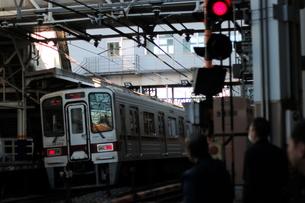 踏切 サラリーマンと停止する電車の写真素材 [FYI03458765]