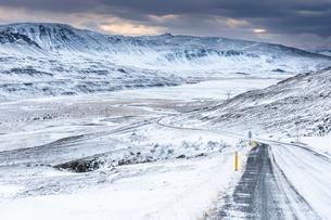 雪山と長く続く道の写真素材 [FYI03458808]