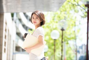 コーヒーとファイルを持っている女性の写真素材 [FYI03458875]