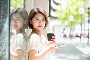 コーヒーを持ってスマホを触っている女性の写真素材 [FYI03458879]