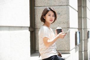 コーヒーを持ってスマホを触っている女性の写真素材 [FYI03458880]