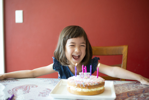 バースデーケーキの前で笑っている女の子の写真素材 [FYI03459284]