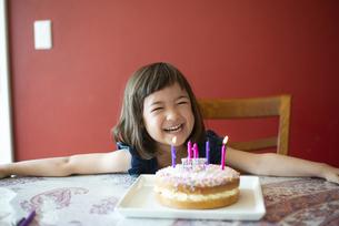 バースデーケーキの前で笑っている女の子の写真素材 [FYI03459299]