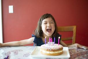 バースデーケーキの前で笑っている女の子の写真素材 [FYI03459336]