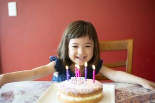 バースデーケーキの前で笑っている女の子の写真素材 [FYI03459337]