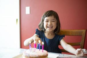 バースデーケーキの前で笑っている女の子の写真素材 [FYI03459338]