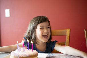 バースデーケーキの前で笑っている女の子の写真素材 [FYI03459339]