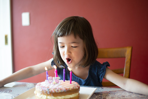 ケーキの上のろうそくを吹き消している女の子の写真素材 [FYI03459340]