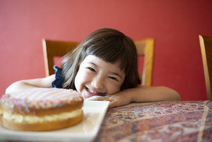 ケーキと一緒に笑っている女の子の写真素材 [FYI03459341]