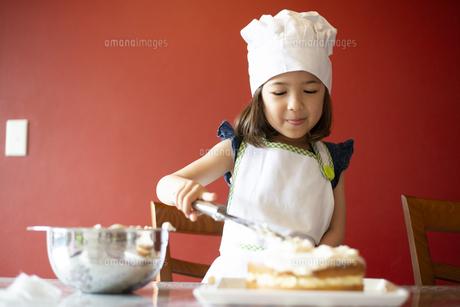 ケーキにクリームを塗っている女の子の写真素材 [FYI03459344]