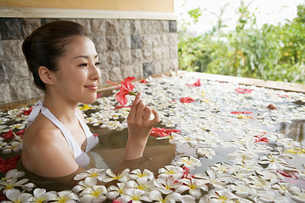 Woman in pool with flower petalsの写真素材 [FYI03460017]