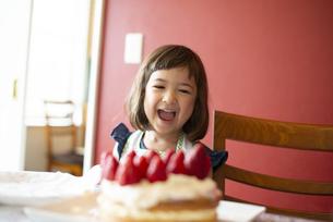 いちごのケーキの前で笑っている女の子の写真素材 [FYI03460059]