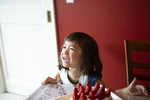 いちごのケーキの前で笑っている女の子の写真素材 [FYI03460187]