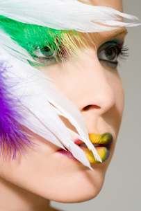 Woman with feathers on her faceの写真素材 [FYI03460265]