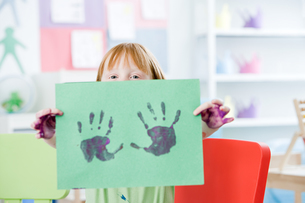 Girl holding up a painted hand printの写真素材 [FYI03460658]
