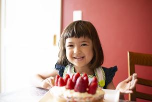 いちごのケーキの前で笑っている女の子の写真素材 [FYI03460699]
