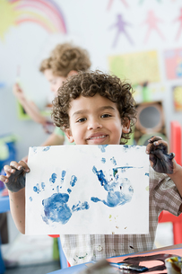 Boy holding up painted hand printの写真素材 [FYI03460707]