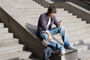 Boy text messaging on stairwayの写真素材 [FYI03460789]