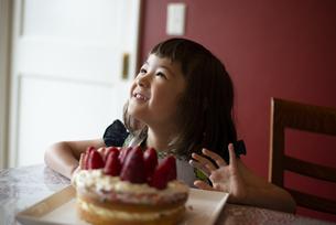 いちごのケーキの前で笑っている女の子の写真素材 [FYI03460935]