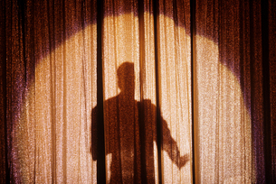 Shadow of a person on a stage curtainの写真素材 [FYI03461237]