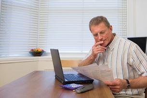 Man doing home financesの写真素材 [FYI03461635]
