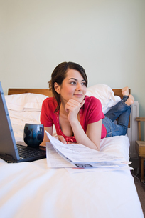 Woman on bed with billsの写真素材 [FYI03461642]