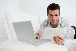 Man with bills and laptopの写真素材 [FYI03461643]