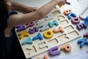 アルファベットの木のおもちゃで遊んでいる子供の手元の写真素材 [FYI03461928]